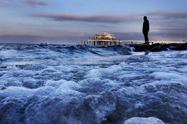 A man stands at the shore of the Baltic Sea in Timmendorfer Strand, northern Germany, Tuesday, October 25, 2016. In background the sea bridge with the new tea house. (Photo by Michael Probst/AP Photo)