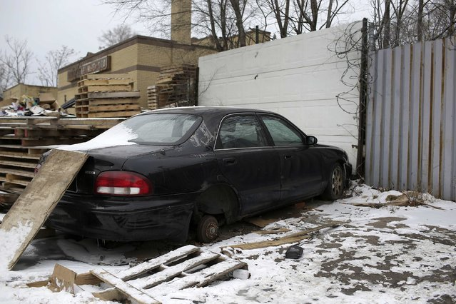 A Mazda 626 with a missing wheel sits next to wood pallets in Detroit, Michigan January 8, 2015. (Photo by Joshua Lott/Reuters)