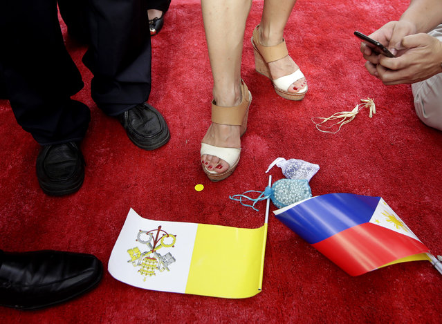 Government officials take photos of their feet on the same spot where Pope Francis stood during the welcoming ceremony Friday, January 16, 2015 at the Presidential Palace grounds in Manila, Philippines. Pope Francis arrived Thursday for a five-day apostolic visit in this predominantly Catholic nation in Asia. (Photo by Bullit Marquez/AP Photo)