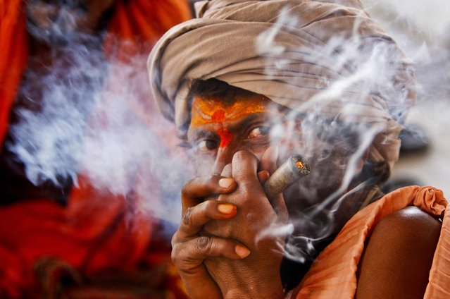 A Hindu holy man smokes as he waits to register for the annual pilgrimage to the Amarnath cave shrine in Jammu, India, on June 28, 2013. Thousands of pilgrims annually visit the remote Himalayan shrine of Amarnath at 12,756 feet above sea level to worship an icy stalagmite representing Shiva, the Hindu god of destruction. (Photo by Channi Anand/Associated Press)