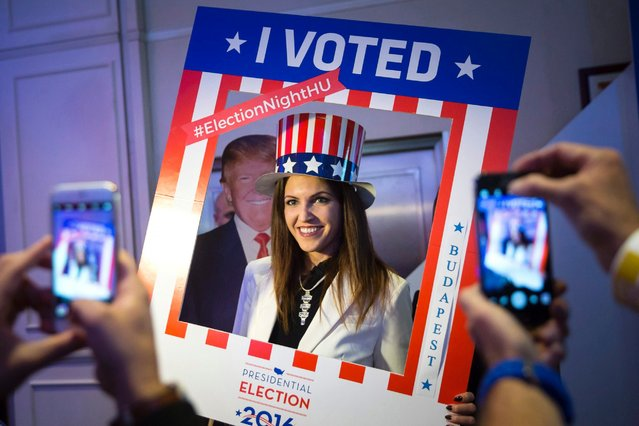 A woman wearing an American patriotic top hat poses for a photograph in the foreground of a cardboard figure depicting Donald Trump, the Republican presidential candidate, during the Election Night Party at the U.S. Embassy in Budapest, Hungary, November 8, 2016. (Photo by Balazs Mohai/EPA)