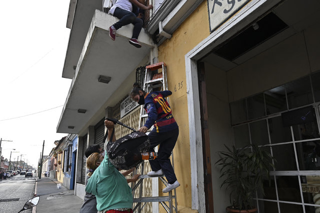A teenager is helped with a ladder as she climbs down from a building to escape the Zafiro I shelter in Guatemala City on February 17, 2021. Ten girls and teenagers who remained in a state shelter escaped for alleged rights abuse. (Photo by Johan Ordonez/AFP Photo)