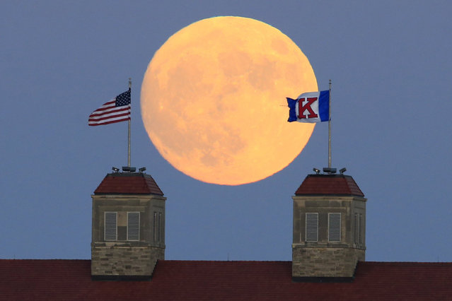 The moon rises beyond flags atop Fraser Hall on the University of Kansas campus in Lawrence, Kan., Sunday, November 13, 2016. Monday morning's supermoon was to be the closest a full moon has been to Earth since Jan. 26, 1948. (Photo by Orlin Wagner/AP Photo)