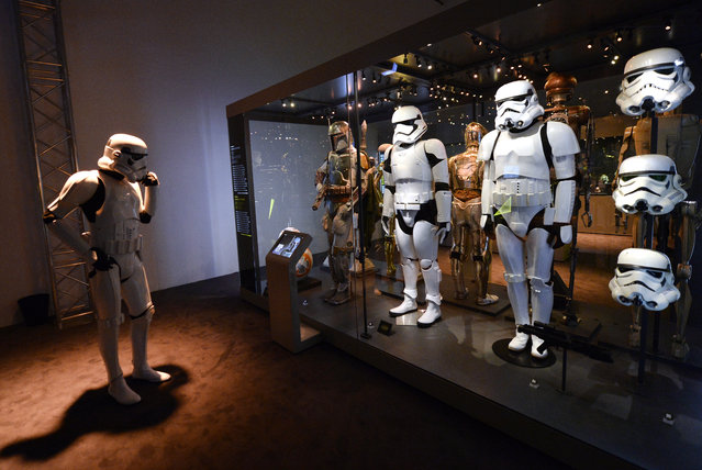 """A member of the """"501st Legion"""" – Star Wars fan club in a Stormtrooper-costume looks at stormtrooper costumes at the 'Star Wars Identities' exhibition in the Museum fuer angewandte Kunst in Vienna, Austria, December 17, 2015. (Photo by Hans Klaus Techt/EPA)"""
