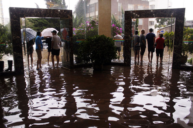 Citizens look on as water flooded streets in a lobby on July 19, 2013 as heavy storm hit Kunming, southwest China's Yunnan province. At least 295 people have been confirmed dead or missing after rainstorms and Typhoon Soulik hit China, causing floods, landslides and buildings to collapse, the government said on July 15. (Photo by AFP Photo)