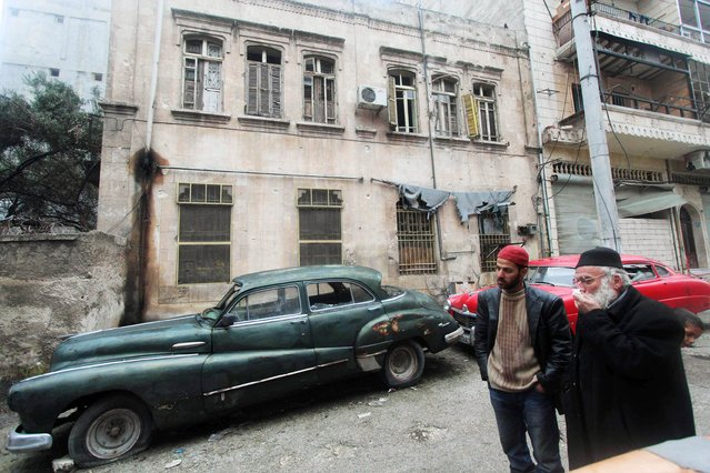 Mohamed Badr al-Din (R) stands in front of his vintage cars along a street where he keeps them, in the al-Shaar neighborhood of Aleppo January 31, 2015. The 66-year-old collector nicknamed Abu Omar inherited the hobby from his father and has a large collection of vintage cars, some of which he says belonged to former Syrian officials and were used in several movies and shows. (Photo by Abdalrhman Ismail/Reuters)