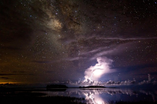 A glorious Milky Way looms over a thunderstorm that lights up the Florida sky. (Photo by Xiao's Photo/Astronomy Photographer of the Year 2018)