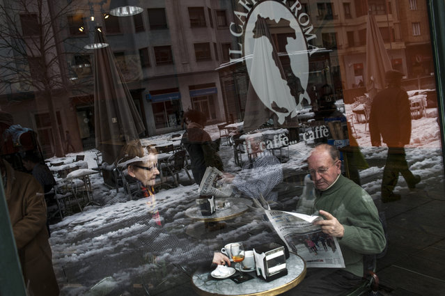 A man reads a newspaper as he enjoys a coffee as the snow reflects on the window of a coffee-bar,  in Pamplona northern Spain, Monday, February 2, 2015. (Photo by Alvaro Barrientos/AP Photo)