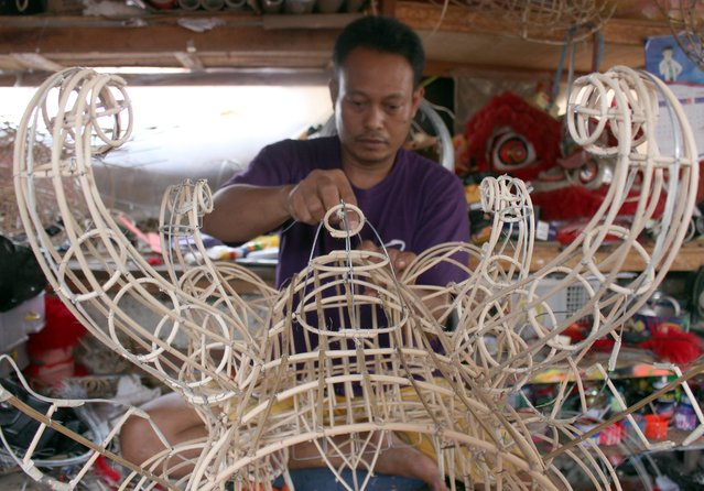 An Indonesian worker makes a dragon mask for the upcoming Lunar New Year at Lily Hambali's dragon and lion masks and custome maker in Bogor, Indonesia, 02 February 2015. The Chinese Lunar New Year, known here as Imlek, is only three weeks away. The whole city is getting decked out to celebrate the event on 19 February 2015. (Photo by Adi Weda/EPA)