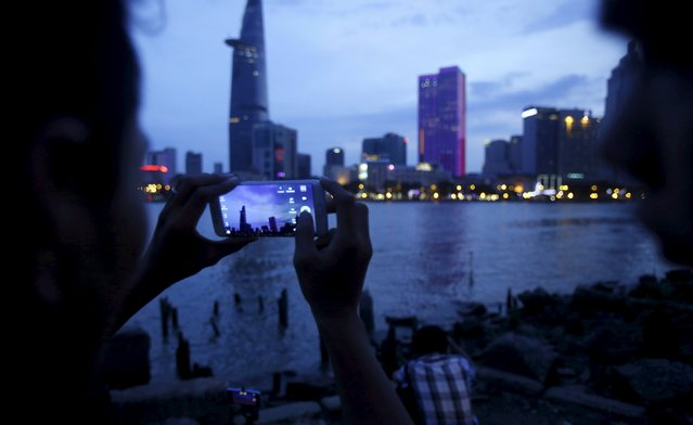 A man takes a picture of buildings across a river with his phone, in Ho Chi Minh City, Viet Nam April 26, 2015. (Photo by Reuters/Kham)