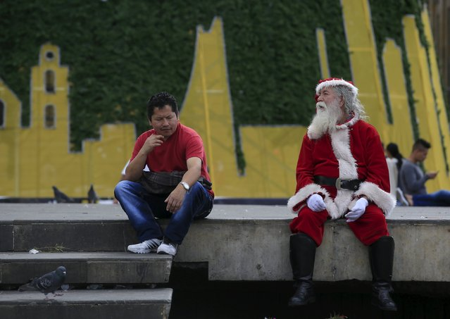 Miguel Antonio Macendes (R), 72-years old, sits at Bolivar Square while wearing a Santa Claus costume in Bogota December 25, 2015. (Photo by John Vizcaino/Reuters)