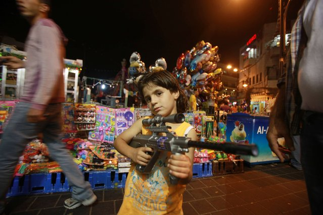 A Palestinian child poses with a plastic toy gun in front of a stall as families shop at a market on the eve of the Eid al-Fitr holiday that marks the end of the Muslim fasting month of Ramadan, on August 7, 2013 in the West Bank city of Ramallah. (Photo by Abbas Momani/AFP Photo)