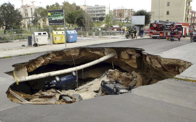 Cars lie in a sinkhole, caused when a road collapsed into an underground cave system, in the southern Italian town of Gallipoli March 30, 2007. There were no injuries in the overnight incident, according to local police. (Photo by Fabio Serino/Reuters)
