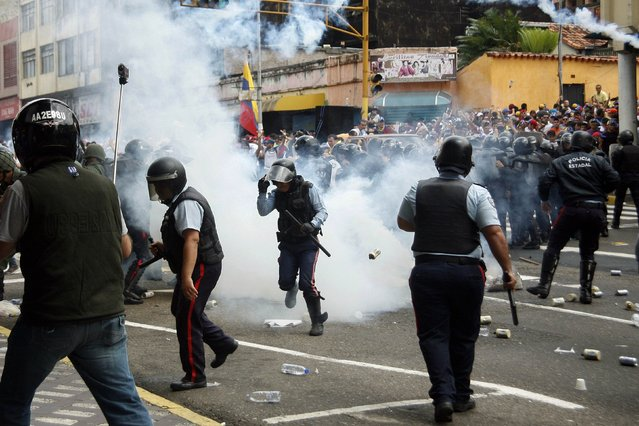 Police runs amidst tear gas as they clash with opposition students during a march against President Nicolas Maduro's government in San Cristobal February 12, 2015. (Photo by Carlos Eduardo Ramirez/Reuters)