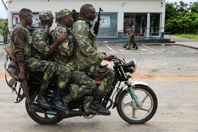 Mozambique army soldiers take a ride on a motorbike in the streets of Palma, Cabo Delgado, Mozambique, 12 April 2021. The violence unleashed more than three years ago in Cabo Delgado province escalated again about two weeks ago, when armed groups first attacked the town of Palma. (Photo by Joao Relvas/EPA/EFE)