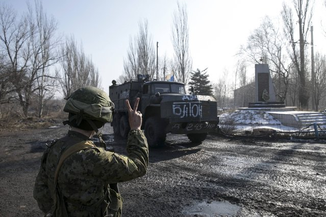 A member of the armed forces of the separatist self-proclaimed Donetsk People's Republic makes a victory sign to his comrades riding a track outside the town of Kondratyevka near Donetsk, Ukraine, February 14, 2015. (Photo by Baz Ratner/Reuters)