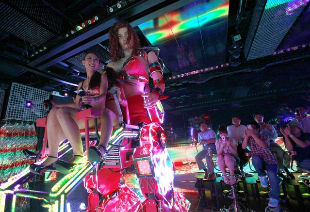 """Bikini-clad women (L) sit as they operate a 3.6 metre-high custom-made female robot as customers take photos, at the """"Robot Restaurant"""" in Kabukicho, one of Tokyo's best-known red light districts, August 16, 2012.  (Photo by Yuriko Nakao/Reuters)"""