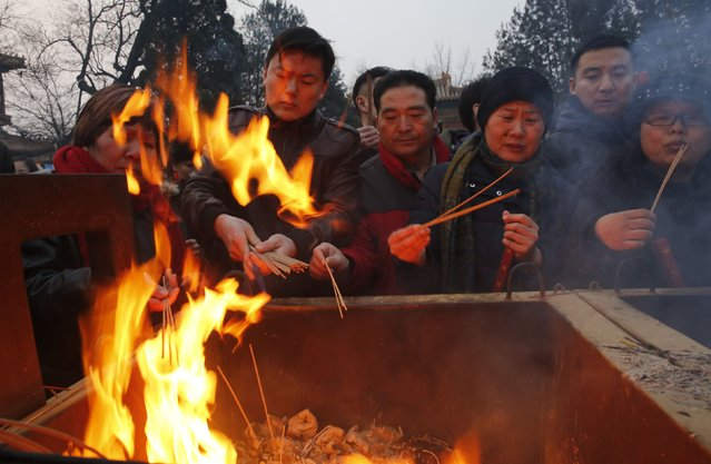 People burn incense as they pray for good fortune on the first day of the Chinese Lunar New Year at Yonghegong Lama Temple, in Beijing, February 19, 2015. (Photo by Kim Kyung-Hoon/Reuters)