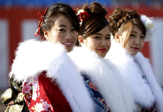 Japanese women wearing kimonos pose for pictures as they attend a Coming of Age Day celebration ceremony at an amusement park in Tokyo January 11, 2016. (Photo by Yuya Shino/Reuters)