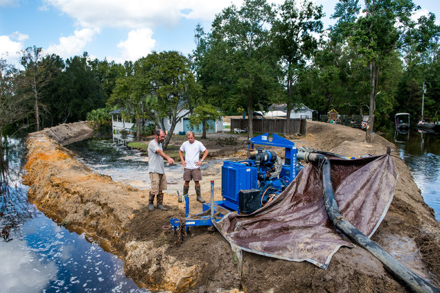 Jason Johnson, left, and homeowner Archie Sanders work to build a temporary levee to hold back floodwaters caused by Hurricane Florence near the Waccamaw River on September 23, 2018 in Conway, South Carolina. Floodwaters are expected to continue to rise in Conway over the next two days. (Photo by Sean Rayford/Getty Images)