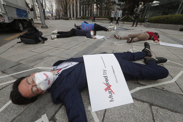 South Korean peace activists lie on a street to pay tribute to the victims of the recent protests in Myanmar, during a rally against Myanmar's military coup in Seoul, South Korea, Friday, March 26, 2021. (Photo by Ahn Young-joon/AP Photo)