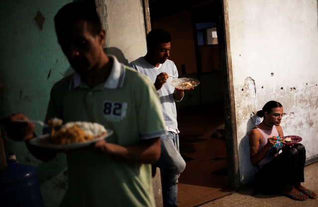 Patricia (R), who is among members of lesbian, gay, bisexual and transgender (LGBT) community, that have been invited to live in a building that the roofless movement has occupied, eats, in downtown Sao Paulo, Brazil November 10, 2016. (Photo by Nacho Doce/Reuters)