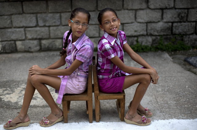"In this Sept. 29, 2013 photo, nine-year-old twin sisters Camila, left, and Carla Rodriguez pose for a portrait along their street in Havana, Cuba. 12 sets of twins live along two consecutive blocks in western Havana, ranging in age from newborns to senior citizens. ""We love living on this block because we have twin friends"", said Carla. (Photo by Ramon Espinosa/AP Photo)"
