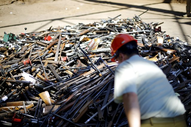 A policeman inspects a pile of confiscated weapons before they were destroyed at a foundry in Santiago, Chile, January 18, 2016. (Photo by Ivan Alvarado/Reuters)