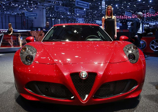 A model poses next to new Alfa Romeo 4C during the second press day ahead of the 85th International Motor Show in Geneva March 4, 2015. REUTERS/Arnd Wiegmann