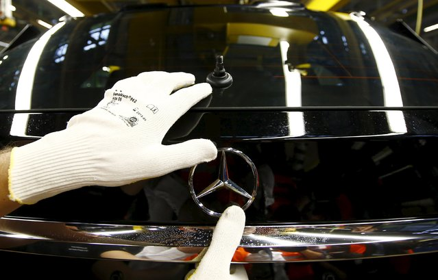 An employee of German car manufacturer Mercedes Benz adjusts the brand's characteristic star on a GLA model at their production line at the factory in Rastatt, Germany, January 22, 2016. (Photo by Kai Pfaffenbach/Reuters)