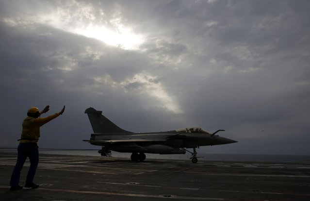 A yellow dog deck officer signals to the pilot of a Rafale fighter jet after it landed,aboard France's Charles de Gaulle aircraft carrier in the  Gulf, January 27, 2016. (Photo by Philippe Wojazer/Reuters)