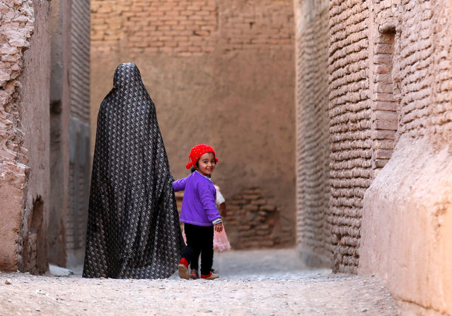 An Afghan woman walks with a child in the old city of Herat province, Afghanistan October 15, 2018. (Photo by Mohammad Ismail/Reuters)