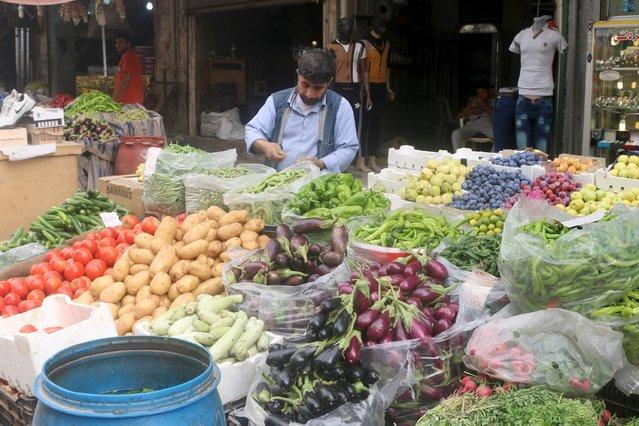 A vegetables vendor arranges produce in Al-Shaar neighborhood of Aleppo, Syria September 7, 2015. (Photo by Abdalrhman Ismail/Reuters)