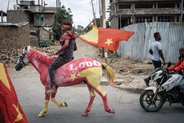 A man rides on a horse painted in the colour of the Tigray flag to celebrate the return of soldiers of Tigray Defence Force (TDF) in Mekele, the capital of Tigray region, Ethiopia, on June 29, 2021. (Photo by Yasuyoshi Chiba/AFP Photo)