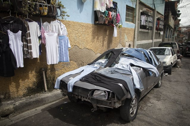Laundry is laid out flat on an out of commission car, on a street in the Petare neighborhood of Caracas, Venezuela, Thursday, June 10, 2021. (Photo by Ariana Cubillos/AP Photo)