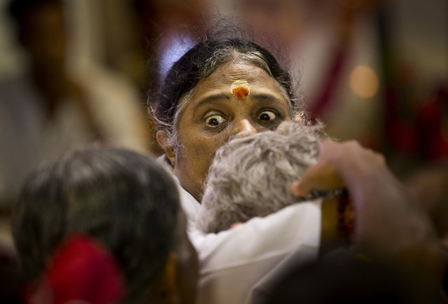 """Indian spiritual leader Mata Amritanandamayi reacts as she hugs to bless a devotee during a prayer meeting in New Delhi, India, Monday, March 30, 2015. Known among her followers as """"Amma"""", which means """"mother"""" in several Indian languages, Amritanandamayi has devotees in India and the rest of the world. She is also popularly known as the Hugging Saint. (Photo by Saurabh Das/AP Photo)"""