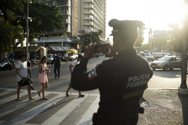 A federal police officer takes a photo of his colleague directing traffic on April 1, 2015 in Acapulco, Mexico. (Photo by Jonathan Levinson/The Washington Post)
