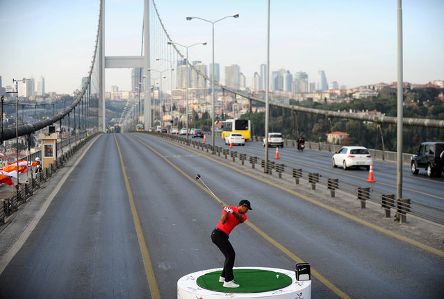 U.S. golfer Tiger Woods hits a ball as he poses during an event to promote the upcoming Turkish Airlines Open golf tournament, on the Bosphorus Bridge that links the city's European and Asian sides, in Istanbul, on November 5, 2013. (Photo by Bulent Kilic/AFP Photo)