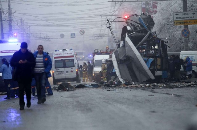 Ambulances line up a site of a trolleybus explosion, background, in Volgograd, Russia Monday, December 30, 2013. A bomb blast tore through the trolleybus in the city Volgograd on Monday morning, killing at least 10 people a day after a suicide bombing that killed at 17 at the city's main railway station. (Photo by Denis Tyrin/AP Photo)