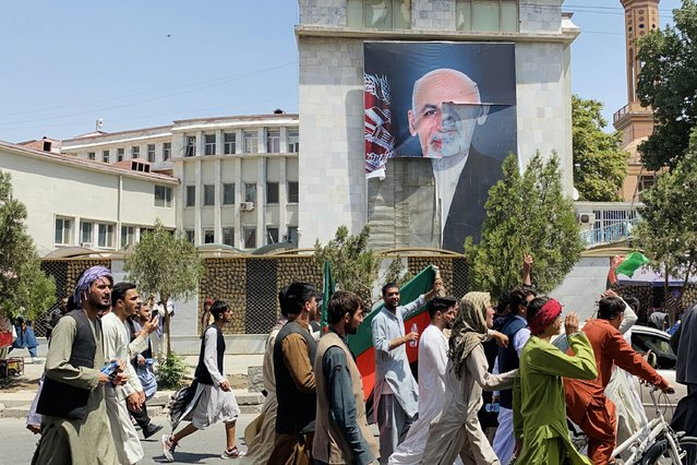 Afghans pass by the poster of Afghan President Ashraf Ghani who fled the country after Taliban took over, as they celebrate the Independence Day in Kabul, Afghanistan, 19 August 2021. Afghanistan's celebrates the 102nd anniversary of its independence from British rule on 18 August. (Photo by EPA/EFE/Stringer)
