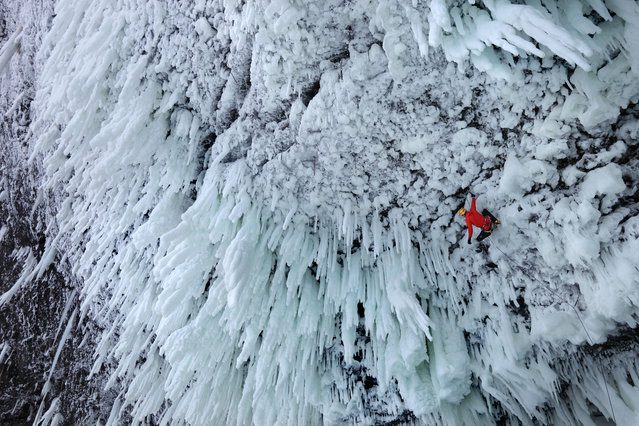 Climbers hang upside down as they climb a giant frozen waterfall. The towering Helmcken Falls in British Columbia, Canada has been dubbed the world's hardest climb and stand at 450ft tall. But despite freezing ice spray, Brit climber Tim Emmett, Raphael Slawinski, from Canada, and Klemen Premrl, from Slovenia, conquered the notorious ice climb. (Photo by Wiktor Skupinski/Barcroft Media)