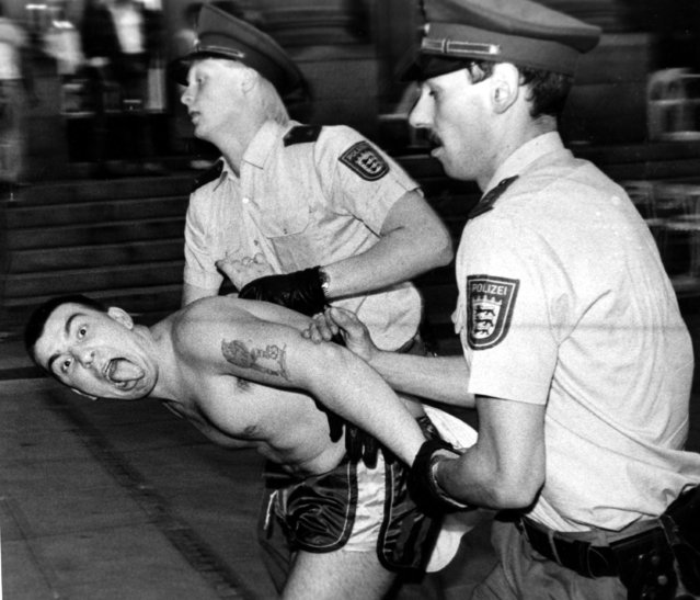 In this Sunday June 13, 1988 file photo West German police officers arrest an English soccer hooligan who sticks out his tongue. Rioting broke out between some 100 hooligans and the police in downtown Stuttgart, West Germany following the European Soccer Championships match between England and Ireland. England was defeated by Ireland 0-1. (Photo by Kraufmann/AP Photo/File)