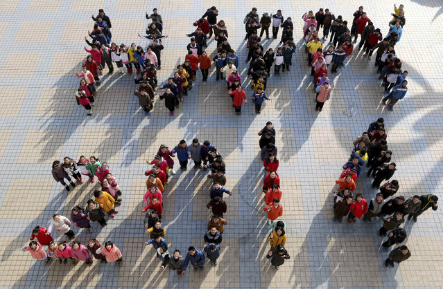 """Students stand to form """"Happy 2014"""" to welcome the upcoming New Year at a middle school in Ma'anshan, Anhui province, December 30, 2013. (Photo by Reuters/China Daily)"""