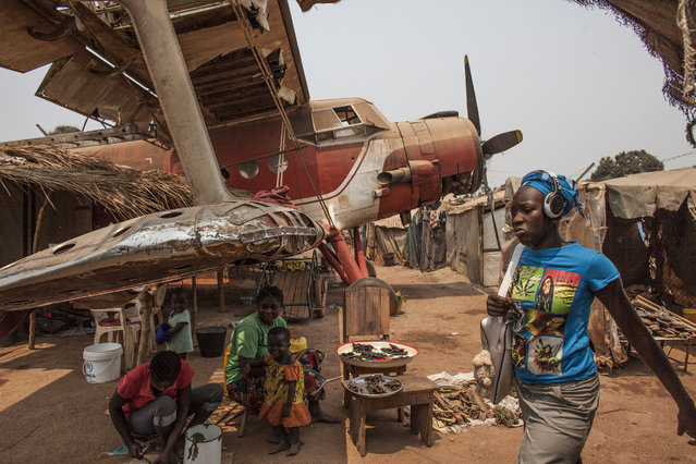 A women sell food under the wing of a plane wreckage being used as housing in M'Poko Internally Displaced Persons camp in Bangui, Central African Republic on Saturday, February 13, 2016. The M'Poko IDP camp, just outside the capitol's airport, currently houses close to 20,000 people displaced due to the ongoing conflict in Central African Republic. The camp was established in late 2013 and contained upto 70,000 people at the height of the crisis in 2014. (Photo by Jane Hahn/The Washington Post)