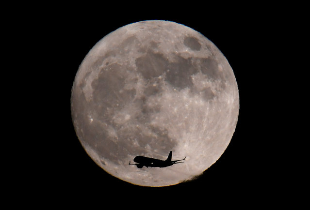 A passenger plane, with a 'supermoon' full moon seen behind, makes its final landing approach towards Heathrow Airport in London, Britain, January 1, 2018. (Photo by Toby Melville/Reuters)