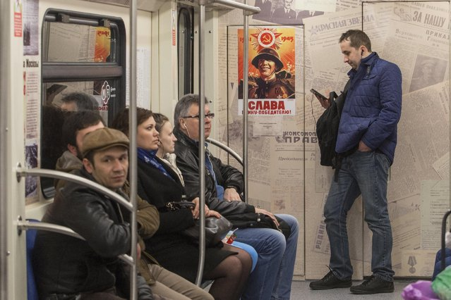 "Passengers take a subway train decorated with World War II era posters during its first trip in Moscow, Russia, Wednesday, April 22, 2015. Russia will celebrate the 70th anniversary of the Victory in WWII on May 9, 2015. The poster reads, ""Glory to soldier the conqueror!"". (Photo by Denis Tyrin/AP Photo)"