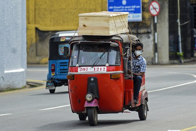 Relatives of a Covid-19 coronavirus victim, transport a coffin on an auto rickshaw to a mortuary in Colombo on August 16, 2021. (Photo by Ishara S. Kodikara/AFP Photo)