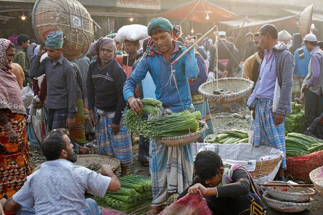 A vendor weighs vegetables as he sells them out at Kawran Bazar in Dhaka, Bangladesh January 25, 2017. (Photo by Mohammad Ponir Hossain/Reuters)