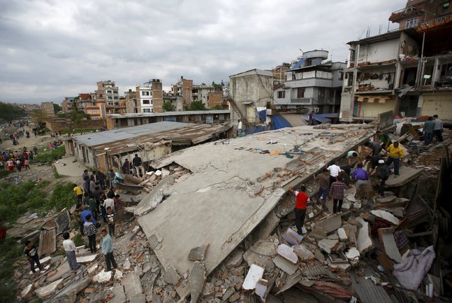 People gather near a collapsed house after a major earthquake in Kathmandu, Nepal April 25, 2015. (Photo by Navesh Chitrakar/Reuters)