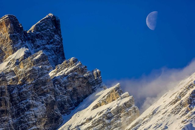 The morning moon is framed by the crests of Mt. Pelmo in San Vito di Cadore in the Italian Alps, on January 23, 2014. (Photo by Domenico Stinellis/Associated Press)